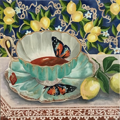 A cup of tea on lace tablecloth sitting in front of a decorative lemon wallpaper