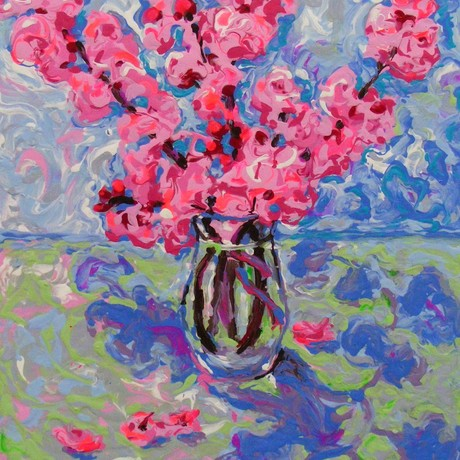 A bunch of vibrant,  pink blossom flowers in a glass vase.