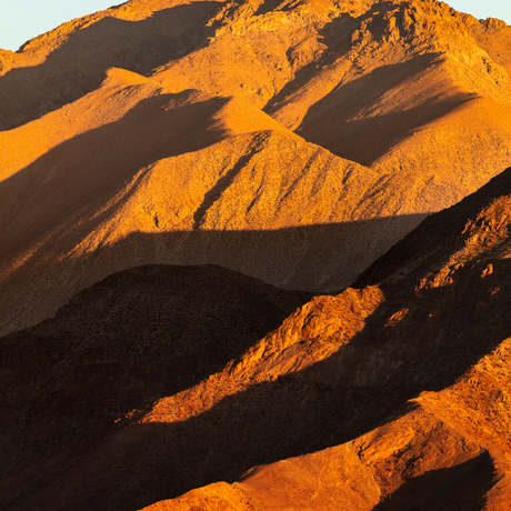Orange and red mountain at sunset with dark, long black shadows cast in different shapes.