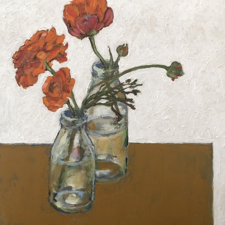 Red flowers in glass bottles on a mustard table.