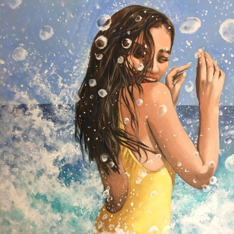 A young woman in a yellow swimsuit being splashed in the surf with lots of bubbles and foam around her.