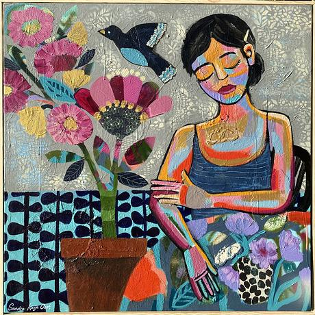Woman with eyes closed sitting at table next to a big flower in a pot plant,  in front of patterned background.