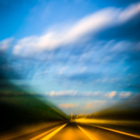 Motion blurred view of highway and clouds speeding towards a blue sky.