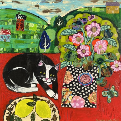 Black and white cat on a red table next to a bunch of stylised pink flowers and leaves in a decorative vase. Background is green hills through a window.