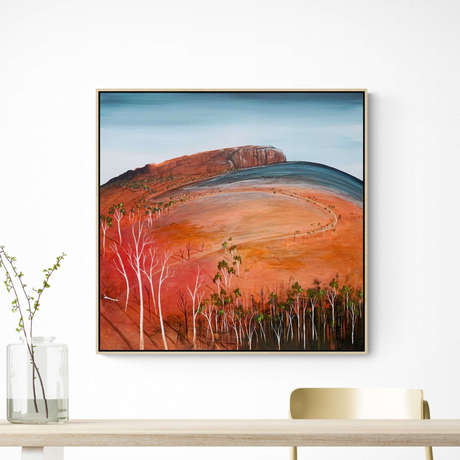 Round hill in earthy burnt orange and red tones with blue and green trees