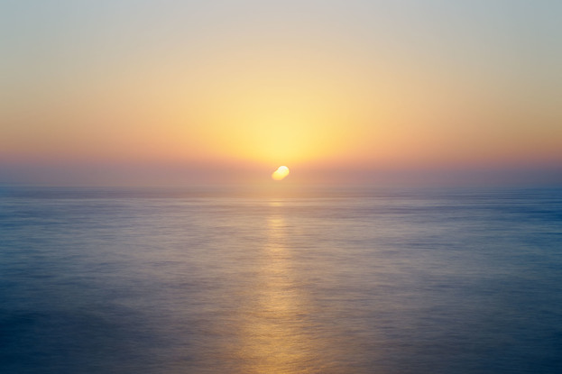 a golden sunrise over the shimmering Pacific Ocean