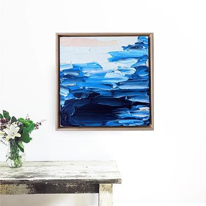 textured abstract seascape in dark blue with a touch of coral framed in oak