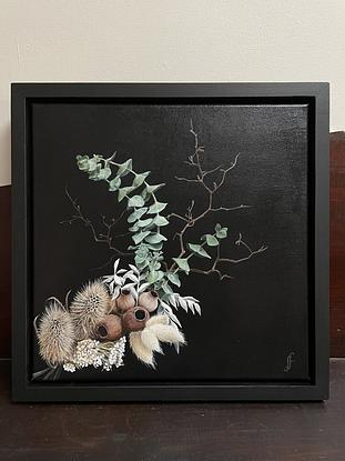 An arrangement of gum leaves, gum nuts, thistle branches, and other dried foliage on a black background.